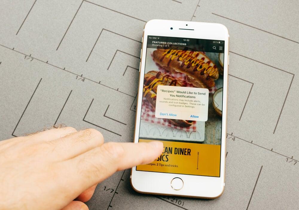 mão masculina indicando smartphone com aplicativo de refeições em tela