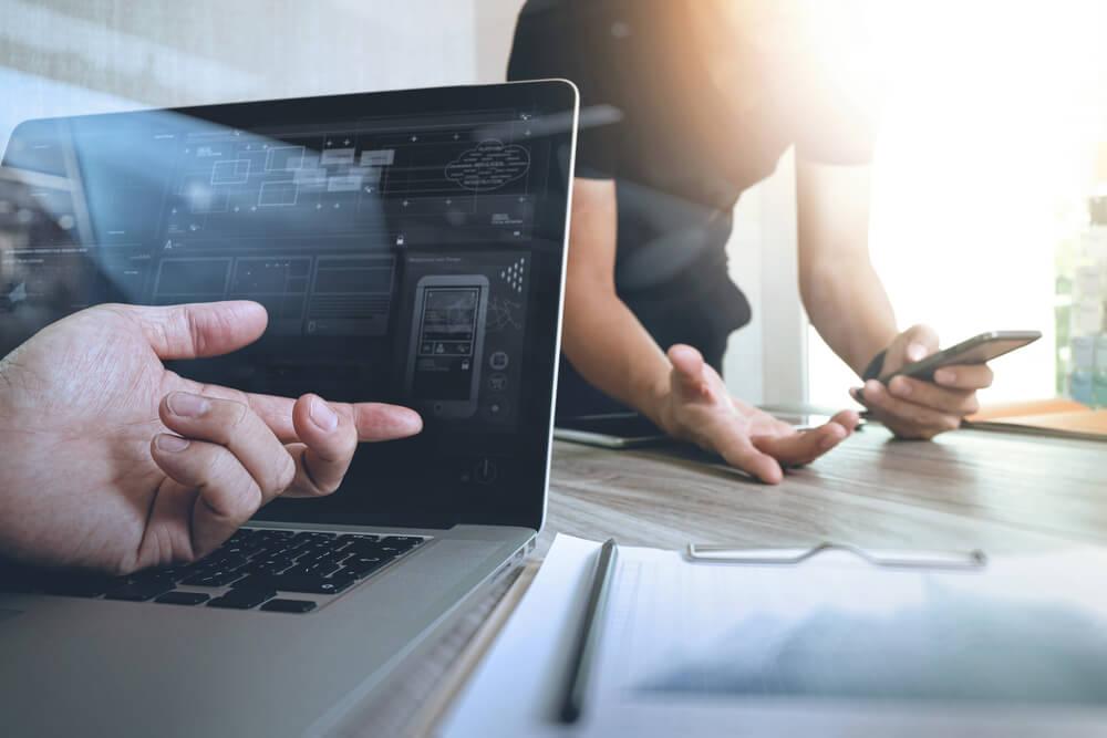 mao masculina indicando tela de laptop e homem ao fundo com smartphone em maos