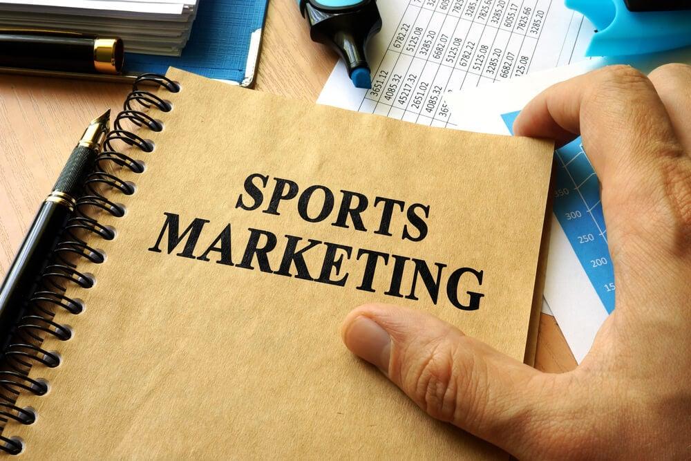 mão masculina junto de caderno sob mesa entitulado marketing de esportes