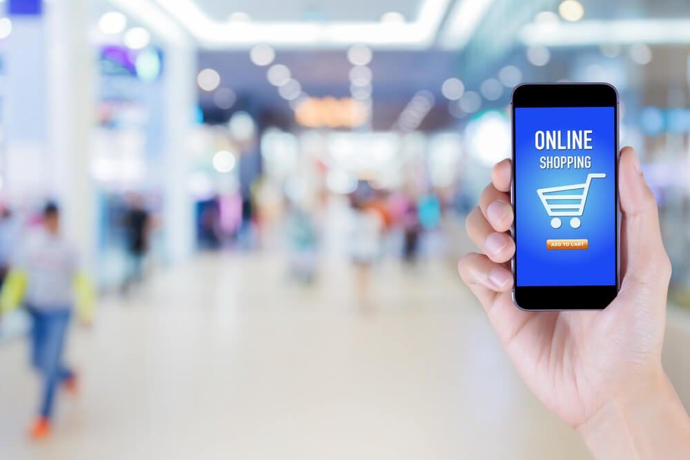 mao masculina segurando smartphone com carrinho de compras e palavra online shopping em tela