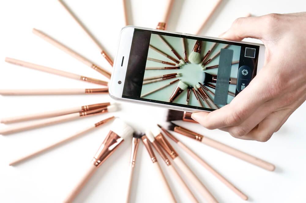 mao segurando smartphone ao tirar foto de produtos sob mesa