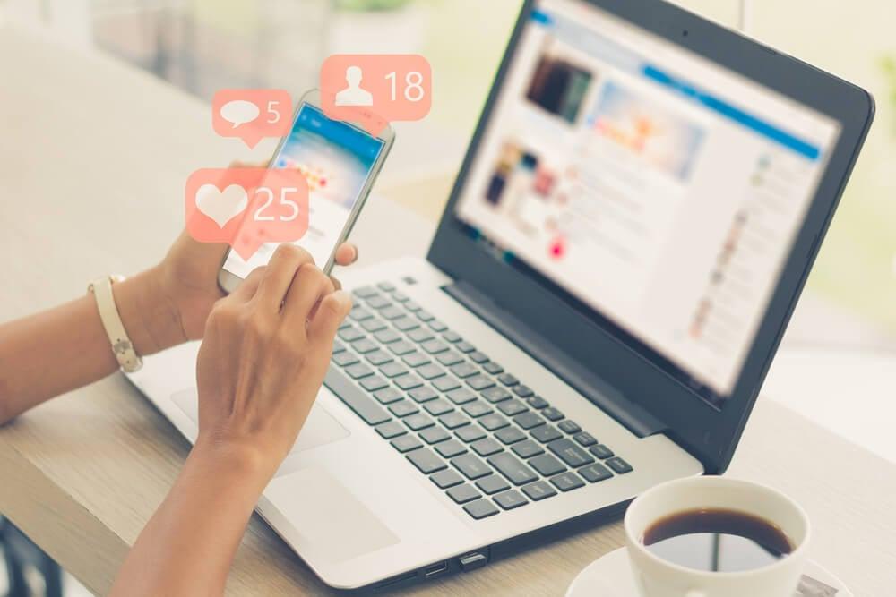 mãos femininas acessando smartphone em frente de laptop