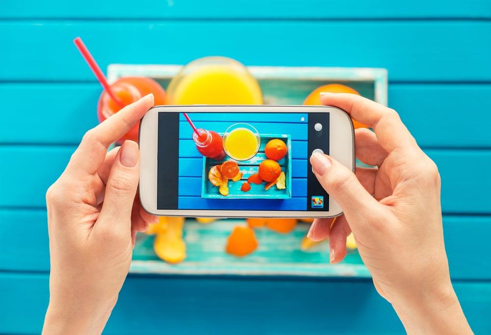 maos femininas segurando smartphone ao tirar fotos de bandeija com alimentos em mesa azul