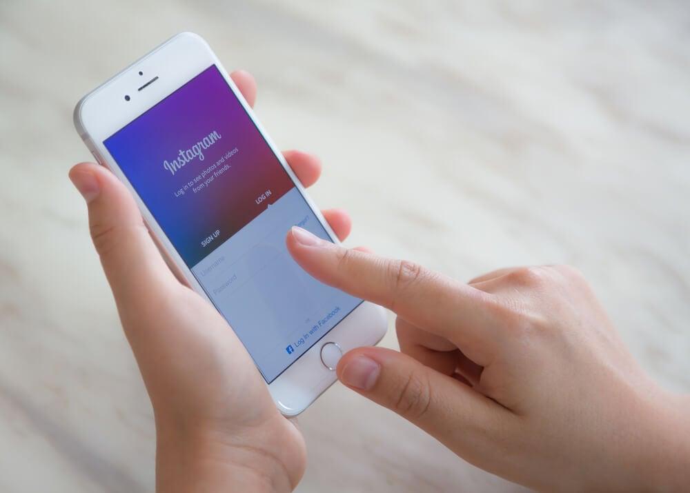 maos femininas segurando smartphone com tela de cadastro do aplicativo instagram