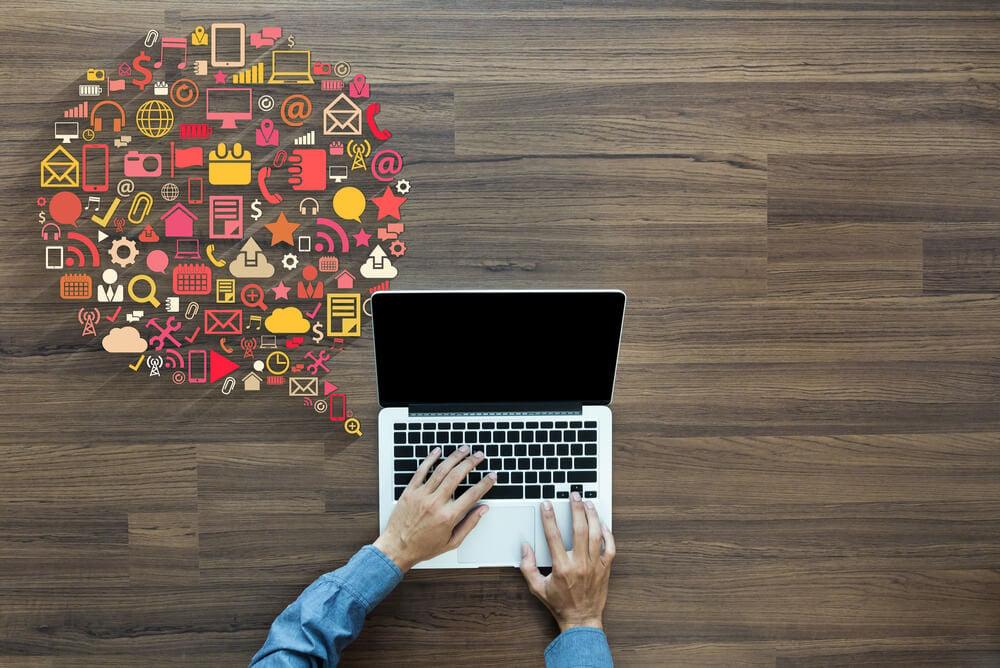 maos masculinas em teclado de laptop com ilustraçao de objetos de produçao ao lado