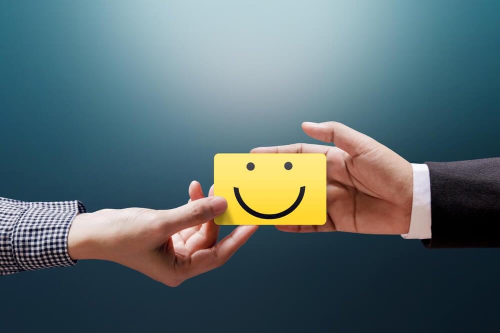 maos masculinas segurando desenho de boneco feliz simbolizando bom relacionamento entre profissional e cliente