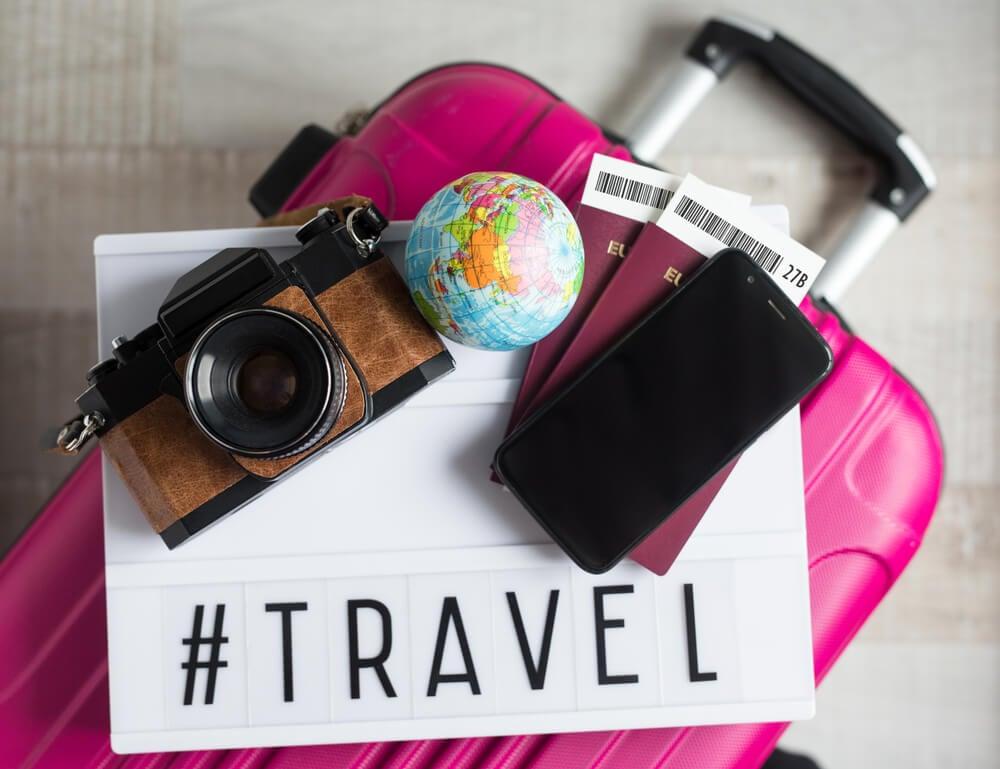 mapa de viagem, globo terrestre smartphone e passaporte junto com hashtag para instagram sobre viagens