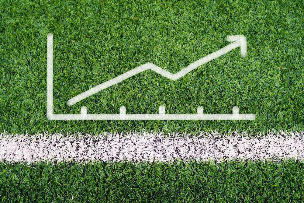 métrica escrita sob grama de campo de futebol