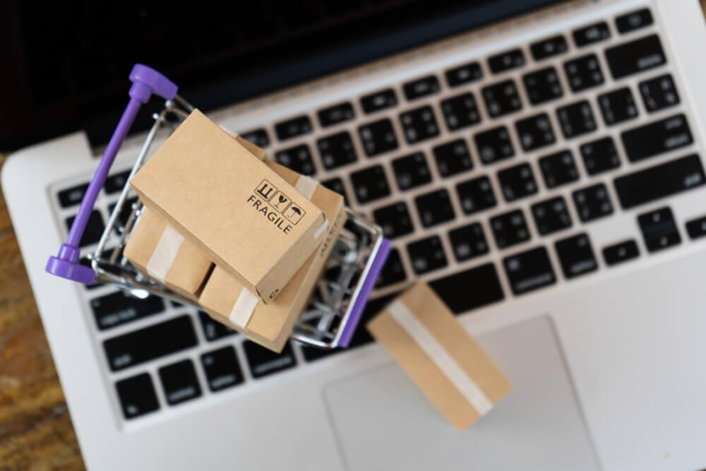 mini carrinho com caixas de produtos sob laptop