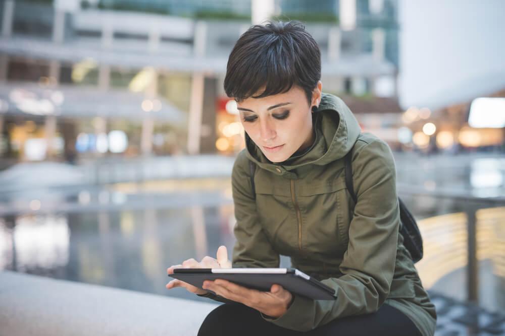 mulher acessando tablet em ambiente externo