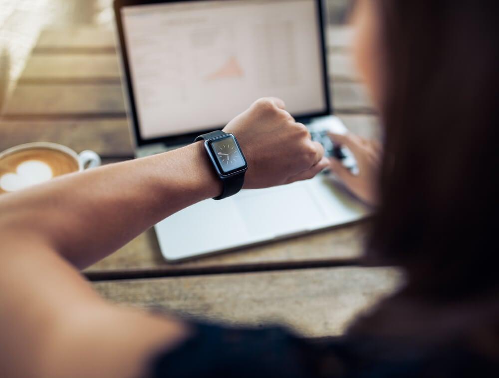 mulher com mao em mouse de laptop focada em relogio de pulso
