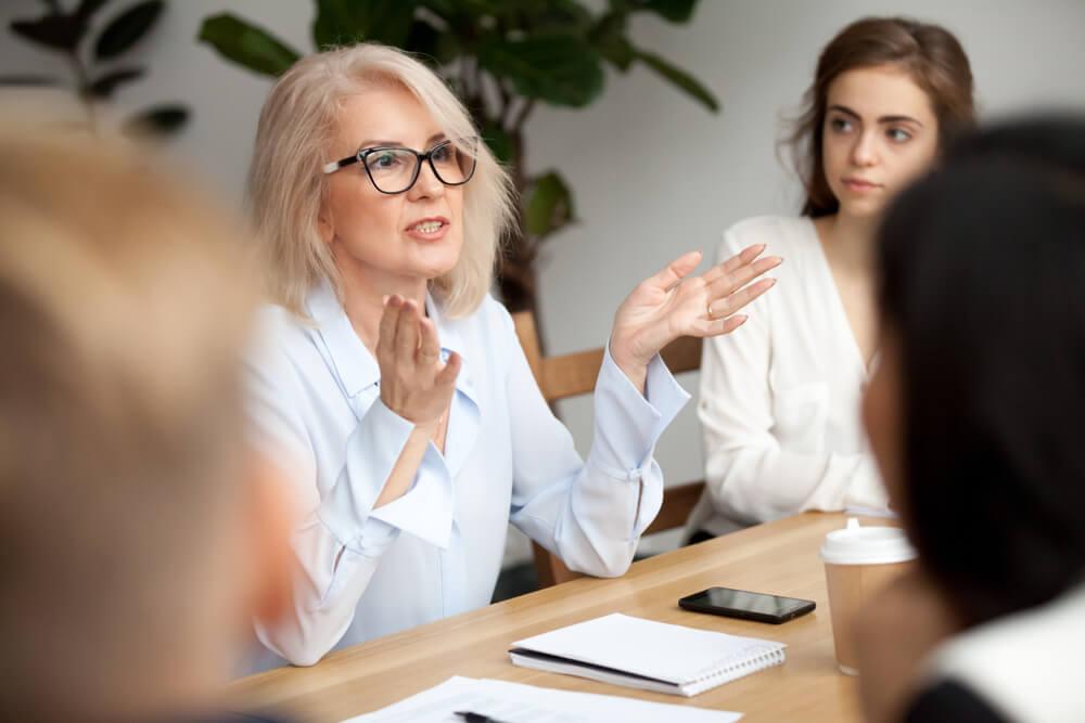 mulher em meio a profissionais de vendas expondo sua opiniao