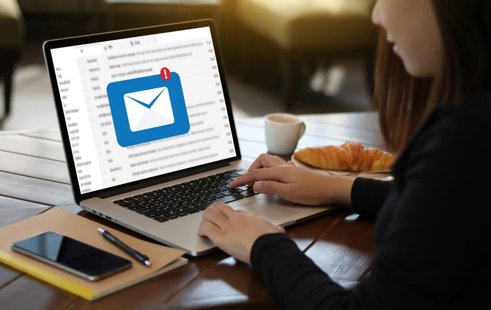 mulher em mesa de escritorio checando emails em laptop com xicara e smartphone ao lado