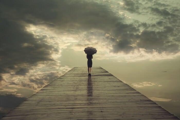 mulher executiva na chuva portando guarda chuva