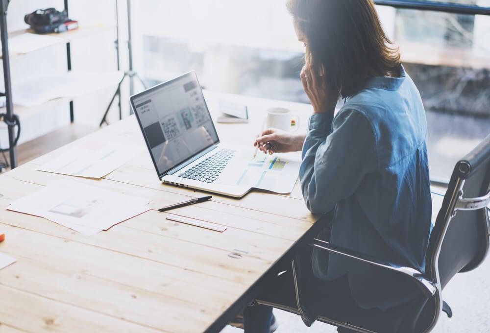 mulher sentada em frente a mesa de escitorio anotando algo ao pesquisar em laptop