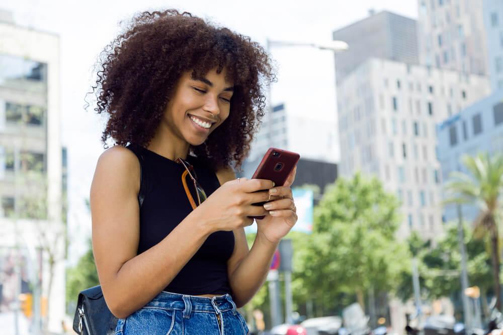 mulher sorrindo ao observar tela de smartphone em lugar publico
