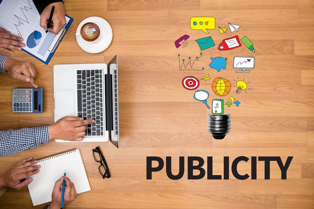 palavra publicity com ilustraçao representando lampada e objetos de trabalho em mesa de escritorio com laptop, prancheta e blcoc de notas