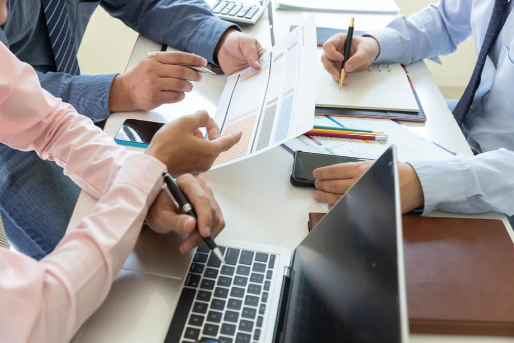 profissionais em meio a planejamento de processo de vendas com laptop e blocos de notas em mesa