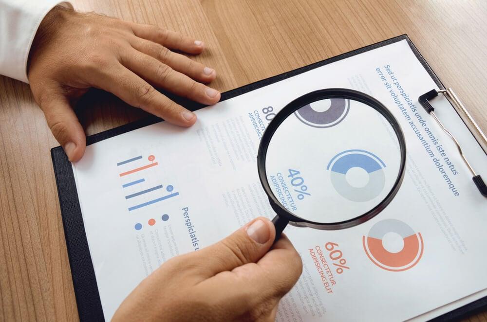 profissional com lupa sob dados de estudo de mercado
