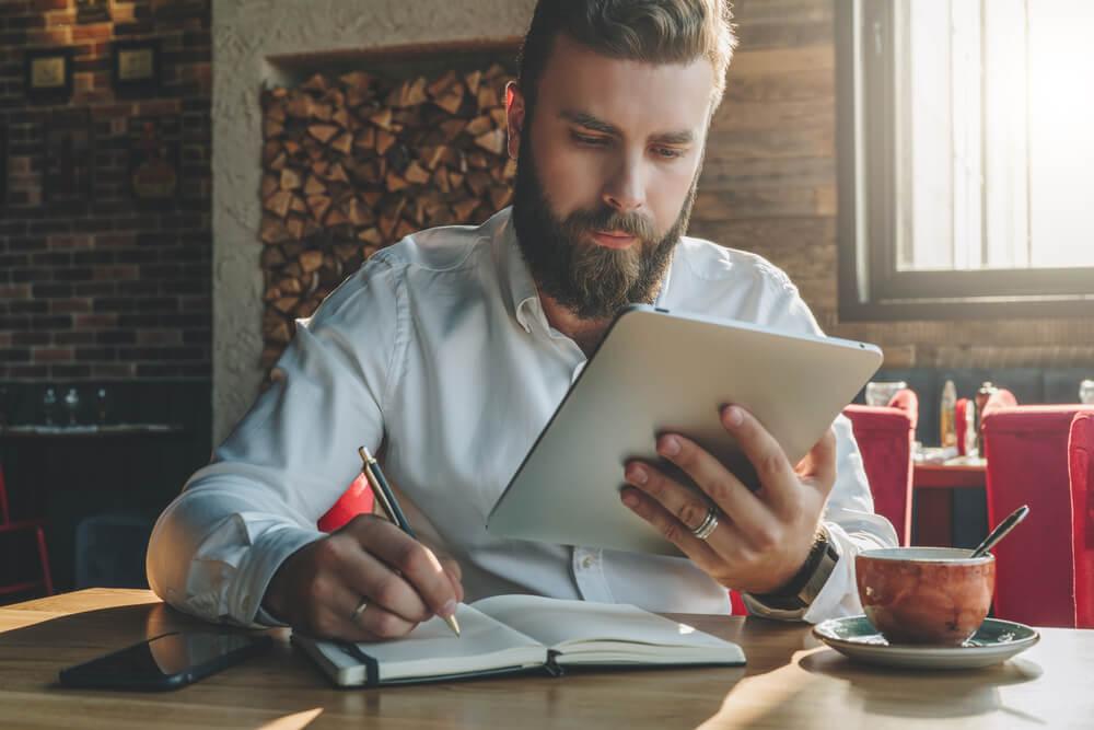 profissional concentrado fazendo anotações e acessando tablet