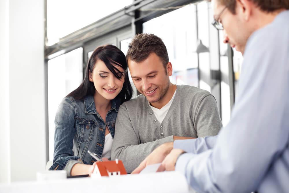 profissional de vendas em conversaçao com clientes que sorriem ao assinar papel