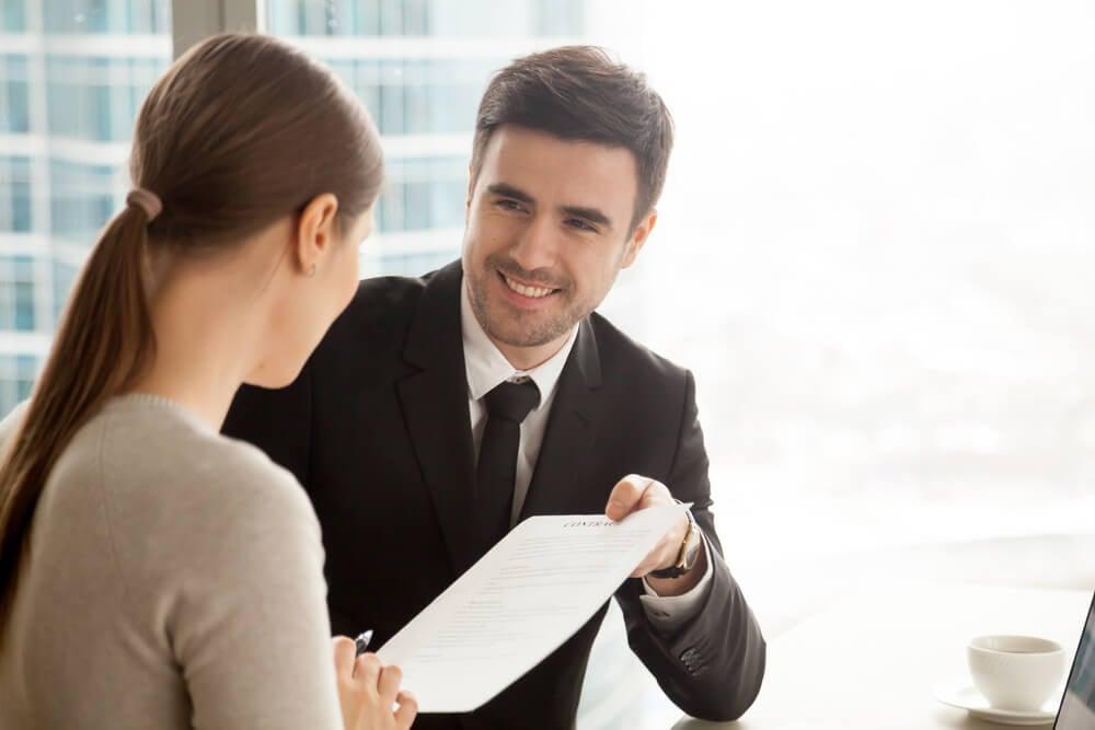 profissional de vendas entregando contrato a cliente