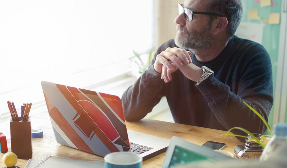 profissional digital pensativo em frente a laptop
