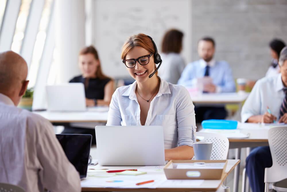 profissional em vendas por telemarketing sorrindo ao teclar em laptop em seu olocal de trabalho