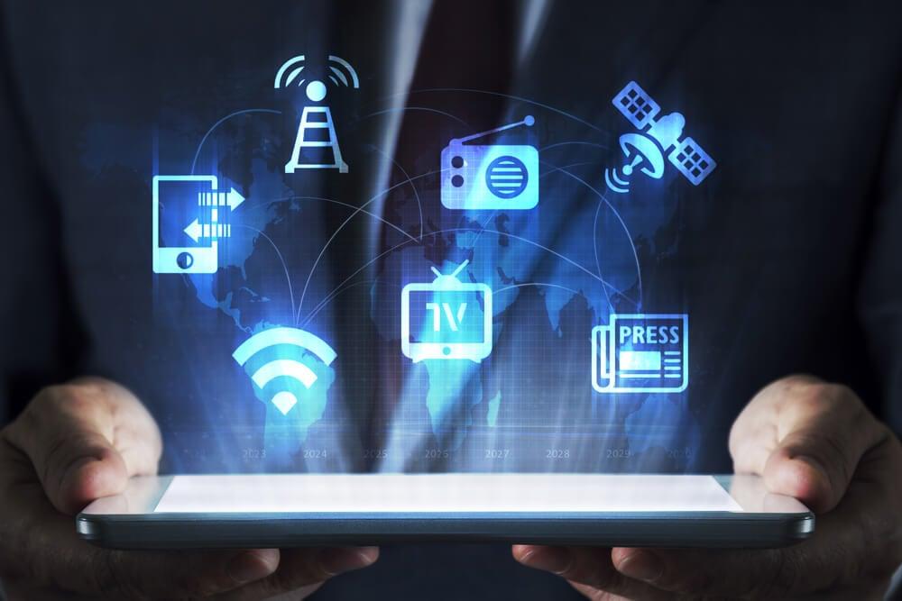profissional segurando tablet com ícones de meios de comunicação e publicidade