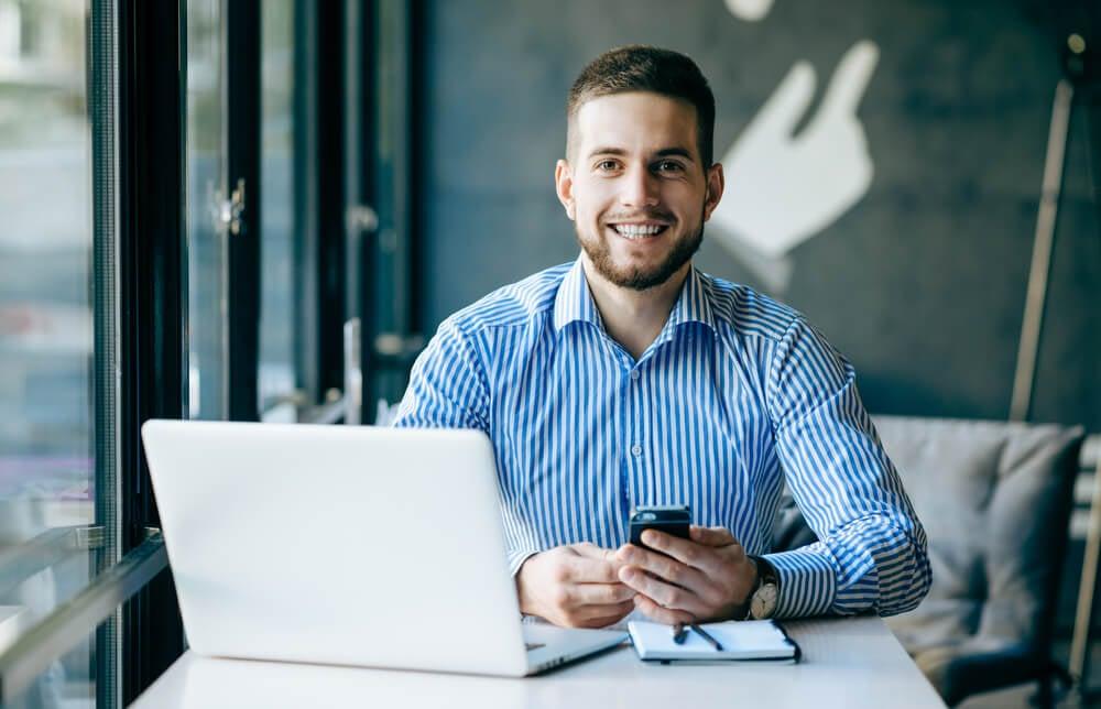 profissional sorridente em frente de laptop e usando smartphone