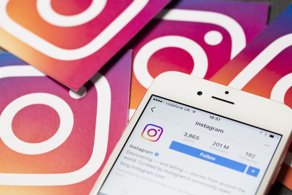 smartphone em meio a simbolos do aplicativo instagram com perfil de instagram em tela