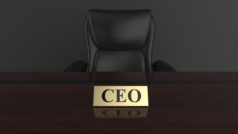 cadeira executiva atras de mesa com cracha sob a mesma com a palavra CEO