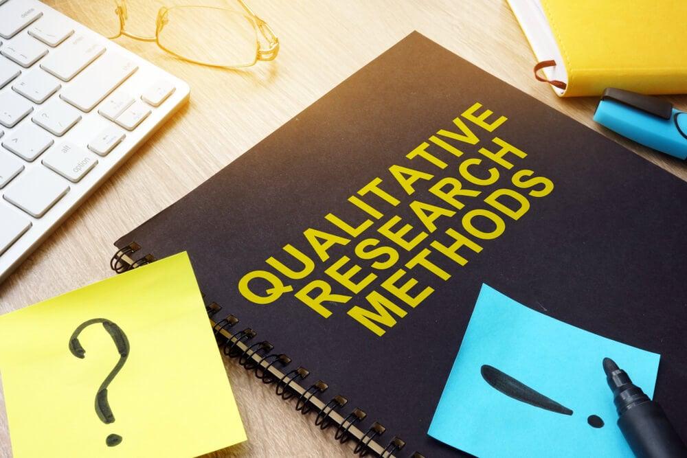 cadernos sob mesa com o título de métodos de pesquisa quantitativa