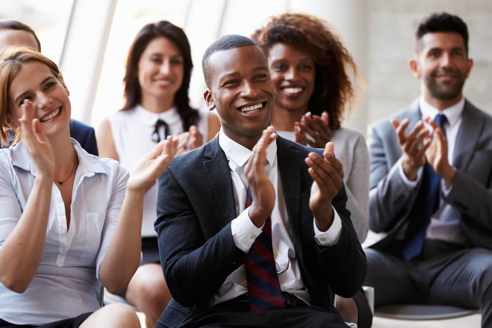 colaboradores de empresa aplaudindo e sorridentes