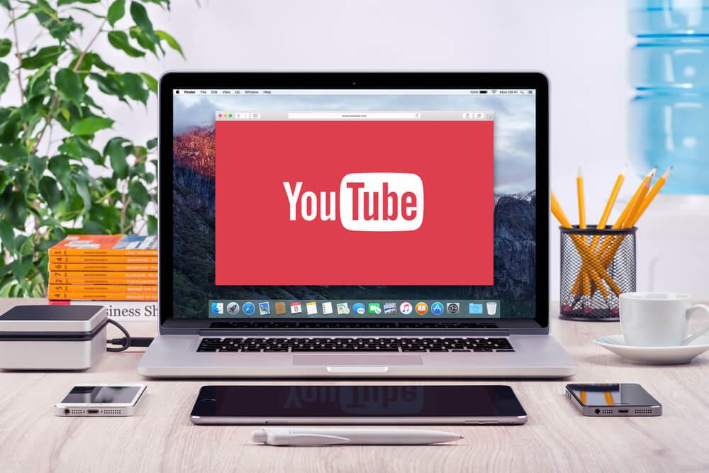 computador em mesa de escritorio com smartphones ao lado e simbolo de aplicativo youtube em tela