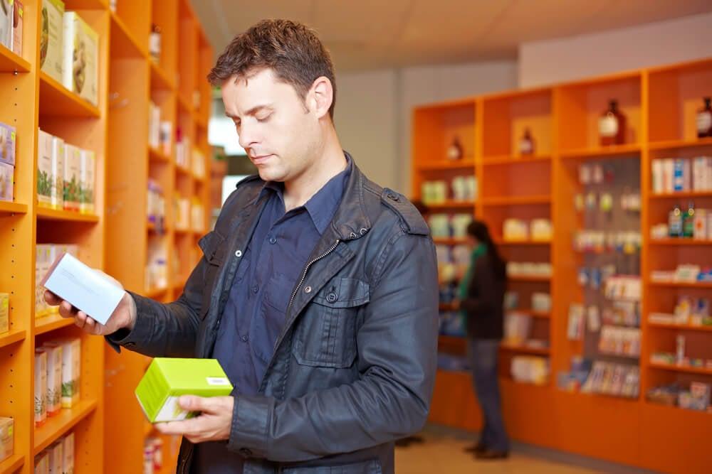 consumidor em frente a prateleira de produtos indeciso entre dois produtos