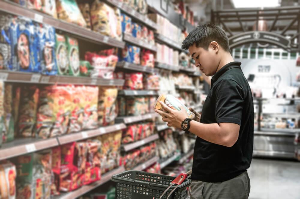 consumidor exigente escolhendo produto em frente a prateleira  e cesta de compras