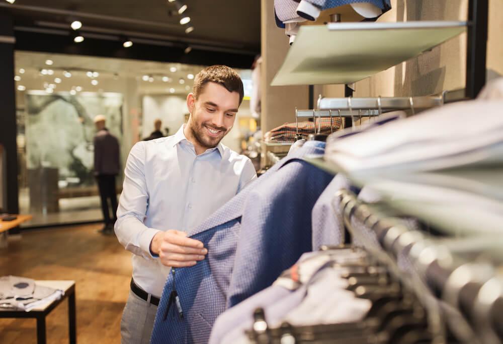 consumidor otimista sorrindo ao escolher roupa em loja