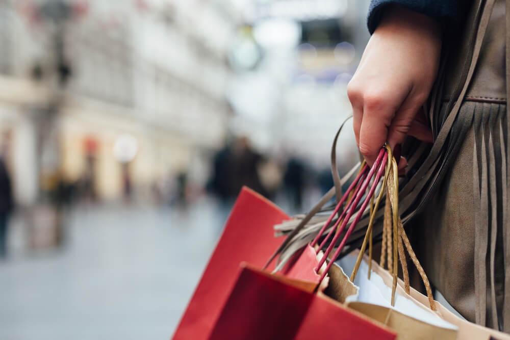 consumidora andando em local publico com sacolas de compras em maos