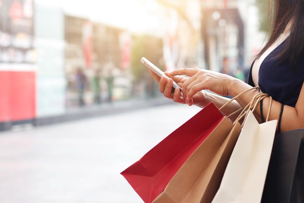 consumidora segurando sacolas de compras e smartphone em local publico