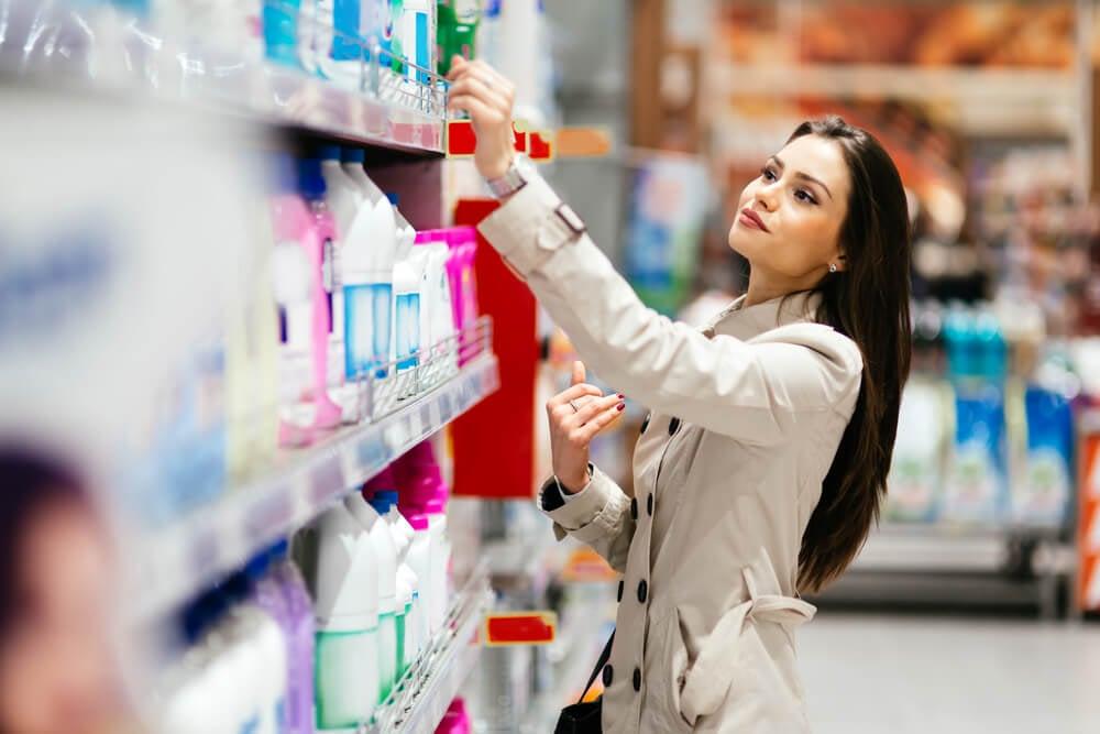 consumidora sorrindo em frente a prateleira enquanto escolhe o melhor produto