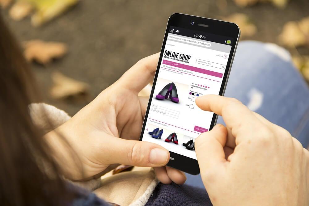 consumidora virtual segurando smartphone em site de compras online