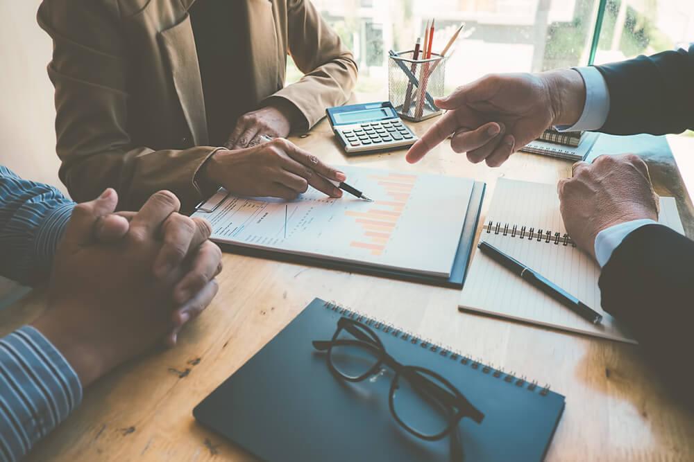 equipe analisando dados e gráficos sobre planejamento empresarial