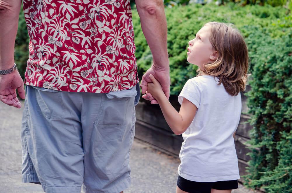 filho sugendo que pai compre produtos enquanto ambos andam em calçada
