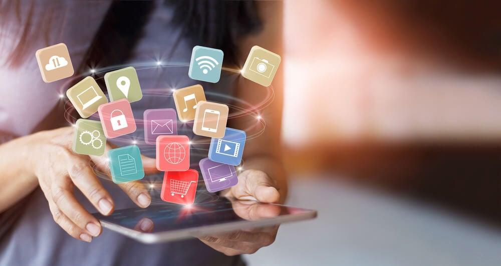 garota acessando tablet junto de simbolos de canais de marketing