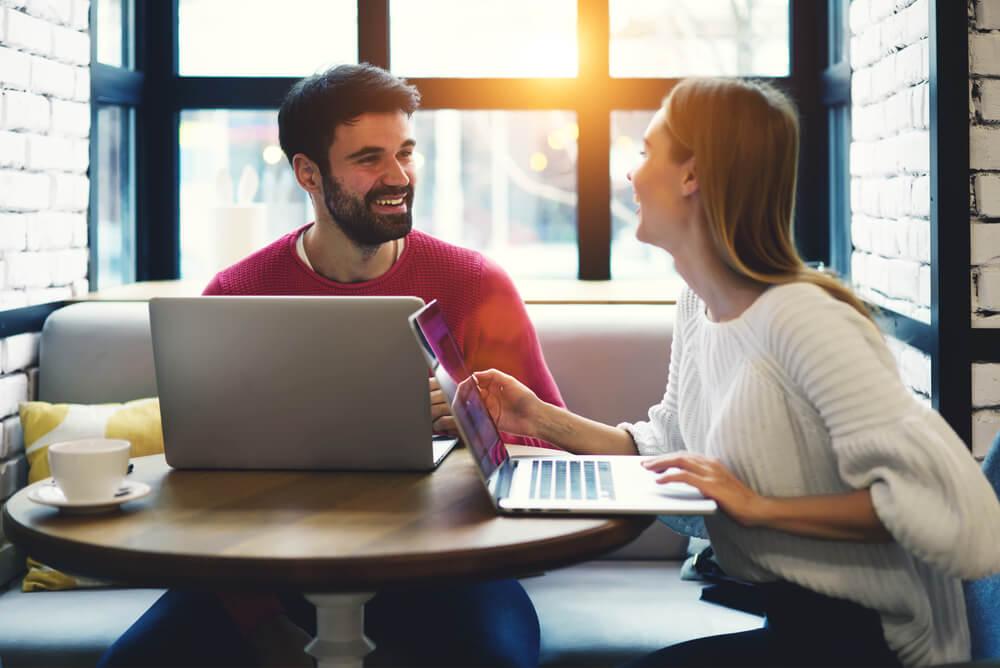 homem e mulher em mesa de cafeteria conversando simbolizando o trabalho em equipe na redaçao publicitaria