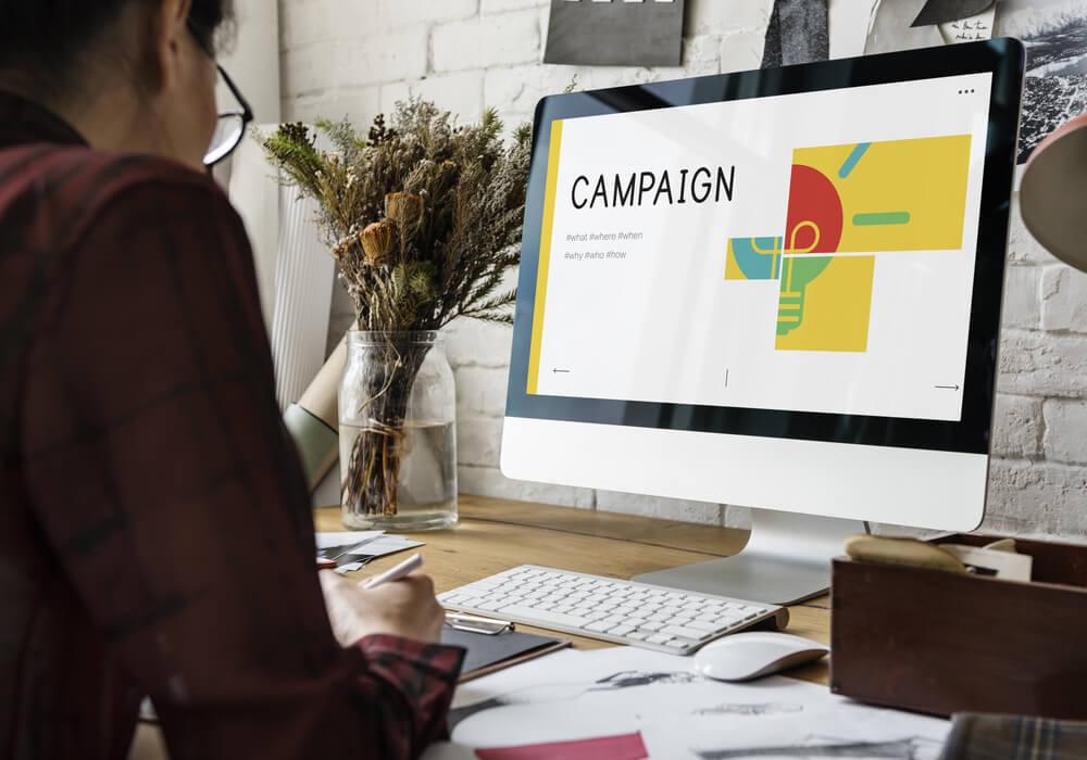 homem em frente a computador com a palavra campaign em tela em mesa executiva