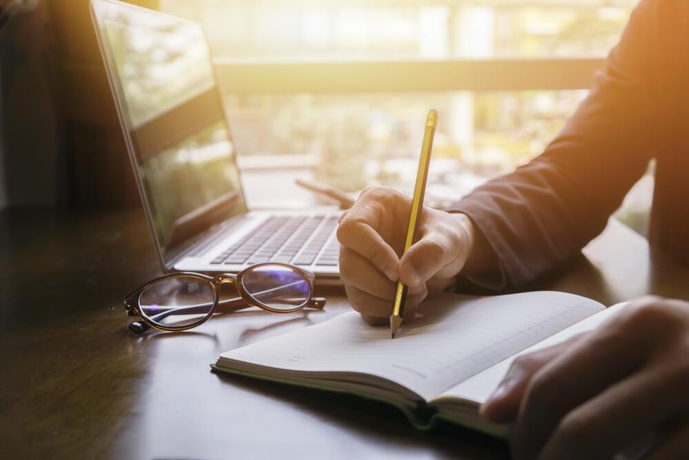 homem escrevendo redaçao publicitaria em bloco de notas com laptop e oculos de grau ao lado