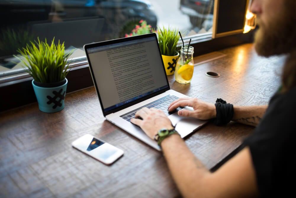 homem escrevendo redaçao publicitaria em laptop sob mesa com decoraçoes