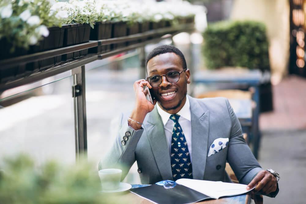 homem executivo sorrindo ao efetuar venda bem sucedida por telefone